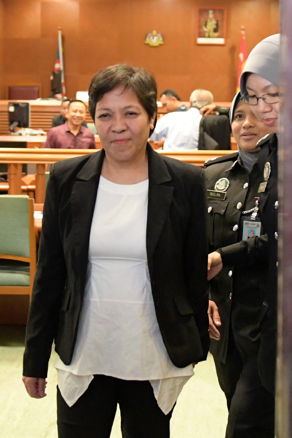 Maria Elvira Pinto Exposto is escorted from the High Court after being cleared of drug trafficking charges in Shah Alam, outside Kuala Lumpur.