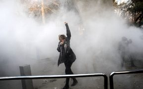 An Iranian woman raises her fist amid the smoke of tear gas at the University of Tehran during a protest driven by anger over economic problems, in the capital Tehran.