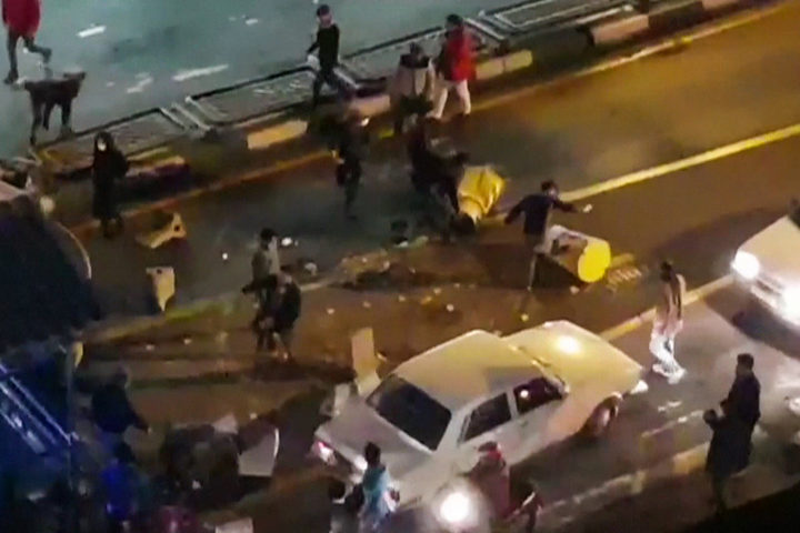 An image grab taken from a handout video released by Iran's Mehr News agency reportedly shows a group of men pushing traffic barriers in a street in Tehran