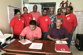 Marshall Islands Minister of Health Kalani Kaneko signs an agreement with the Marshall Islands Red Cross Society for cooperation in first aid training as Red Cross Secretary General Jack Niedenthal (sitting) and staff and volunteers look on.