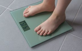 Child with bare feet on a bathroom scale of glass