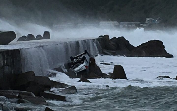 The car was parked on a seawall near Wellington Airport before it ended up stranded on a rock.