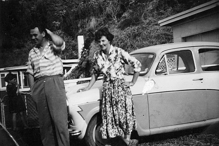 A black and white photo of Bill and Colleen Hopkins, Bruce's parents, leaning on their car.