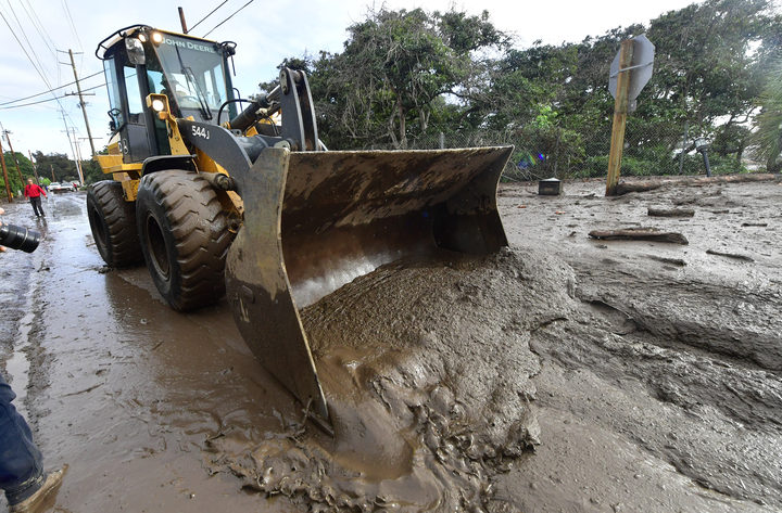 A bulldozer clears mud off the road near a flooded section of US 101 freeway near the San Ysidro exit in Montecito, California.