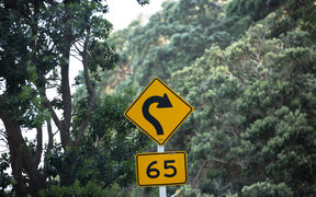 A road sign indicating a 65km speed around a tight corner on a rural road in the Coromandel.