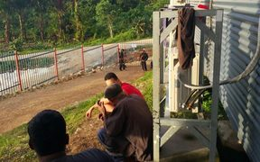 Refugees watch the action unfolding at the gate of Hillside Haus.