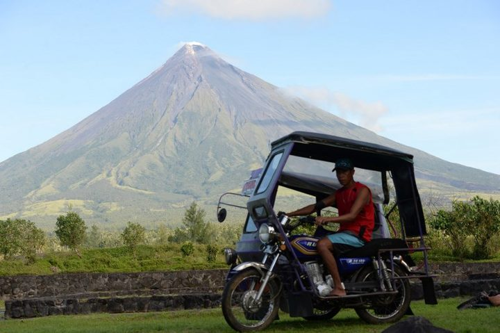 A motorised tricycle speeding past the Mayon volcano