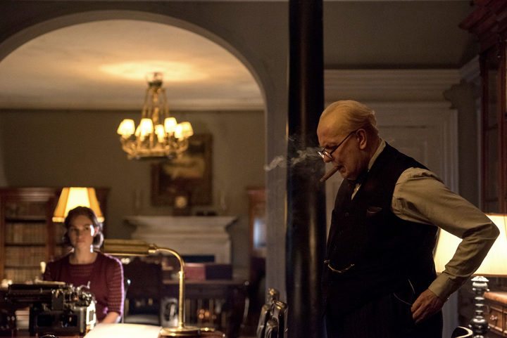Lily James as Elizabeth Layton takes dictation from Gary Oldman as Winston Churchill in Darkest Hour.