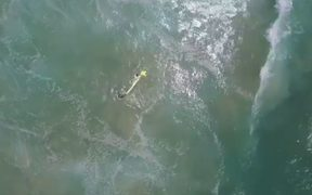 The drone dropped an inflatable rescue device which the two teenagers used to get to shore.