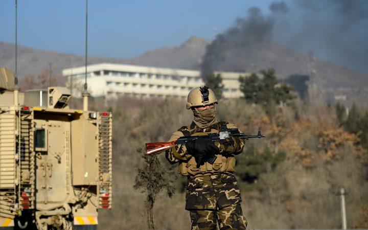 An Afghan security personnel stands guard as smoke billows from the Intercontinental Hotel during a fight between gunmen and Afghan security forces in Kabul on January 21, 2018.