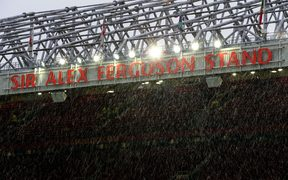 Light snow falling over the Sir Alex Ferguson stand at Old Trafford.