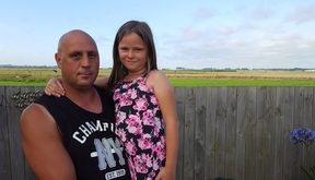 Marcus Walsh, 42, with Kayla Tom, 8, beside their back fence which looks out on to Ohakea Air Force base where the contamination originated.