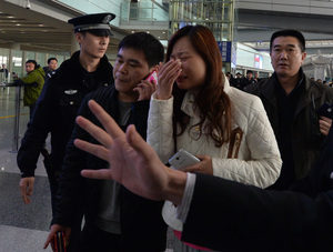 A relative cries at  Beijing Airport after Malaysia Airlines says it is contacting next-of-kin for people on its missing Boeing 777-200 plane.