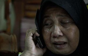 A relative of Malaysia Airlines passengers Norliakmar Hamid and Razahan Zamani, cries at their home.