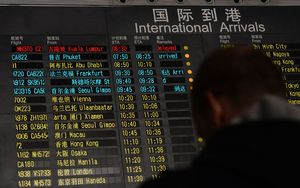 A man stands beside the arrival board showing the flight MH370 at Beijing Airport.