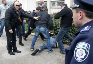 A police officer looks on as pro-Russian activists use a bat to beat a pro-Ukrainian supporter at the Sevastopol rally.