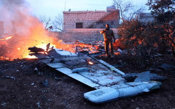 A picture taken on February 3, 2018, shows a Rebel fighter taking a picture of a downed Sukhoi-25 fighter jet in Syria's northwest province of Idlib.