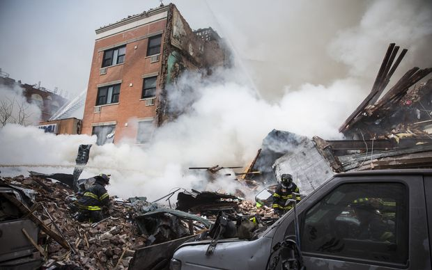 Smoke pours from the debris of a collapsed building in East Harlem.