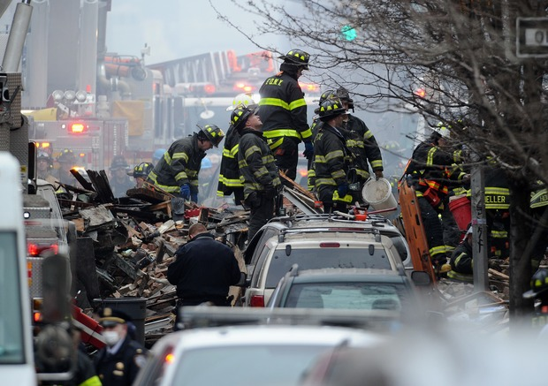 New York City firefighters on a pile of debris at the scene.