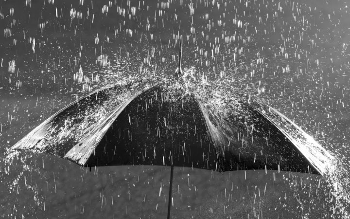 black and white photo of umbrella in heavy rain
