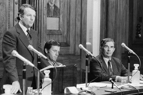 Prime Minister Bill Rowling delivers an outline of the Labour government's economic policy in 1975 with ministers Colin Moyle (centre) and Michael Connelly (right) seated beside him.