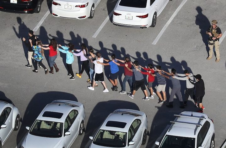 People are brought out of the Marjory Stoneman Douglas High School after a shooting at the school.