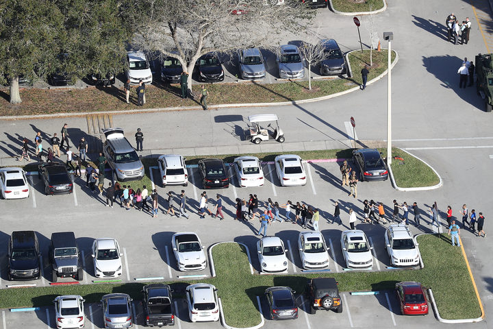 People are brought out of Marjory Stoneman Douglas High School after the shooting at the school that reportedly killed and injured multiple people.