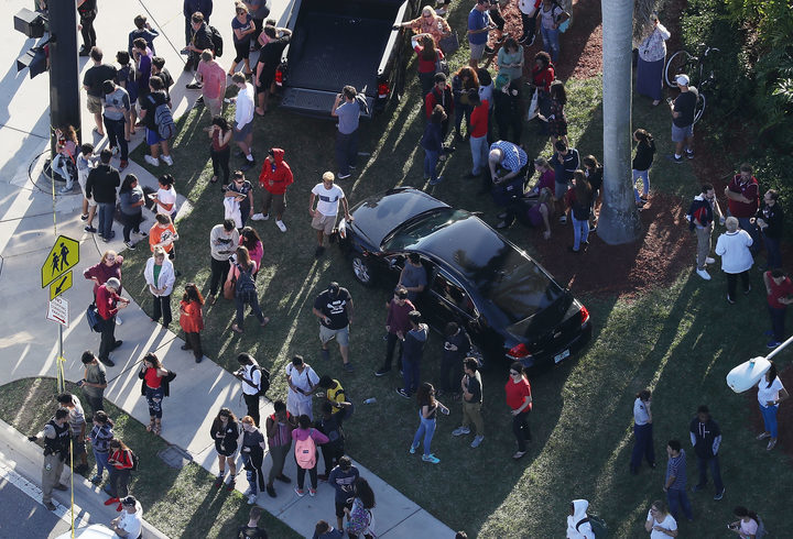 People wait for loved ones as they are brought out of the Marjory Stoneman Douglas High School after the shooting.