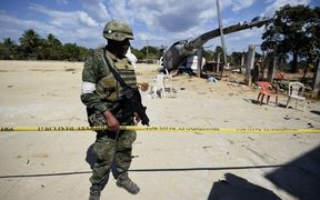 A Mexican soldier stands guard at the site of the accident where a military helicopter fell on a van in Santiago Jamiltepec, Oaxaca state, Mexico.