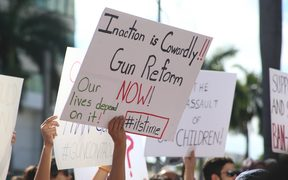 Protesters hold signs during a rally for gun control at the Broward County Federal Courthouse in Fort Lauderdale, Florida on February 17, 2018.