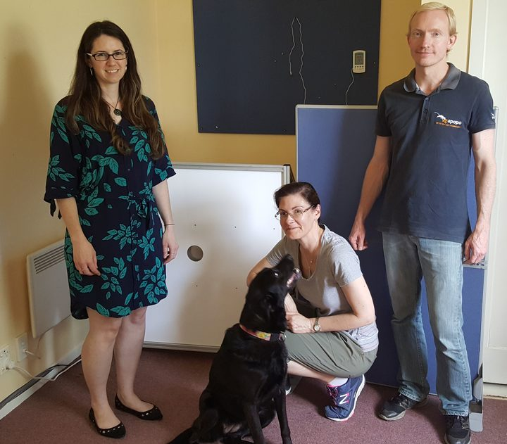 Clare Browne (left), Margaret Crawford with Ruby the black labrador and Tim Edwards standing in front of the experimental set-up - the round hole is the sniffing port for the dogs to put their noses in.