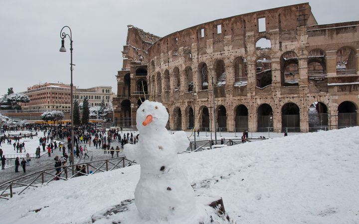 A snowman is seen in front of the ancient Colosseum during a heavy snowfall on February 26, 2018 in Rome.