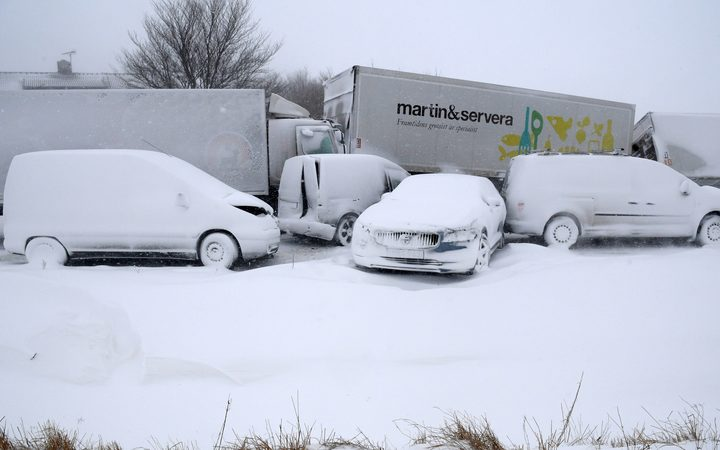 Several trucks and cars, covered with snow, stand deserted after a pileup on February 27, 2018 near Sjobo, southern Sweden.