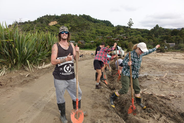 Volunteers help clear mud and debris a week after the storm.