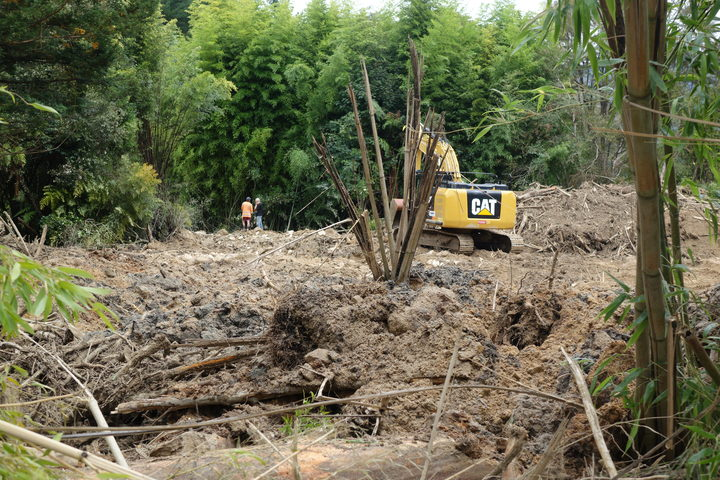 A digger helps clear forestry debris in Marahau after slips and flash flooding from Cyclone Gita.