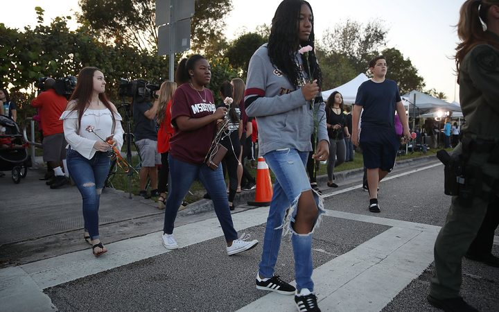 Students walk to Marjory Stoneman Douglas High School as they attend classes for the first time since the shooting that killed 17 people.