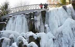 People standing on a bridge above a frozen waterfall at the Bergpark Wilhelmshoehe park in Kassel in central Germany.