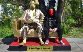Artist Plastic Jesus poses with the gold sculpture of Harvey Weinstein on his infamous casting couch.