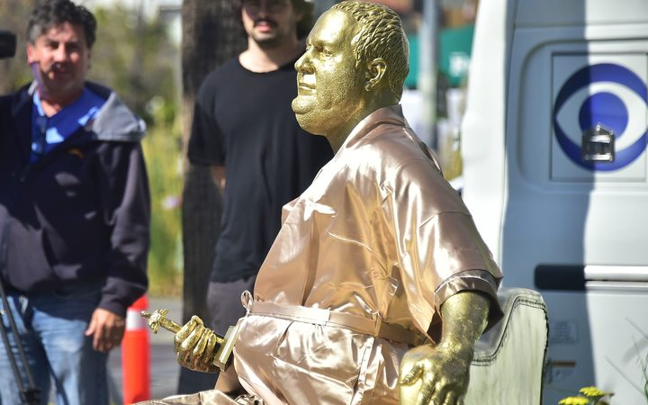 A gold sculpture of Harvey Weinstein on his infamous casting couch holding an Oscar statue is on display in Hollywood.