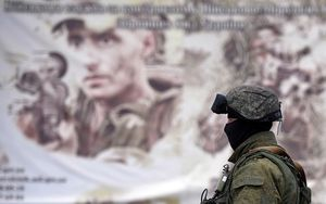 A Russian soldier in front of a Ukrainian army recruitment poster in Crimea.