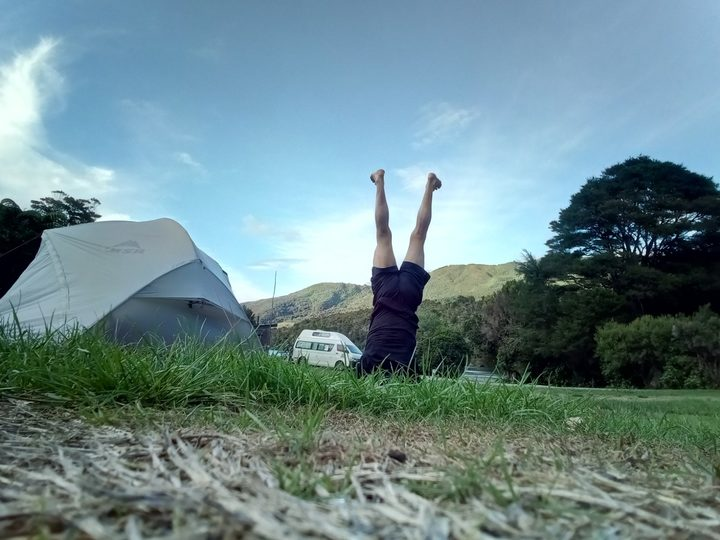 Bruce Hopkins performs a headstand next to his tent.