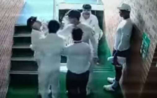 An image from video footage showing Australian players holding David Warner back during an altercation with South Africa's Quintin de Kock.