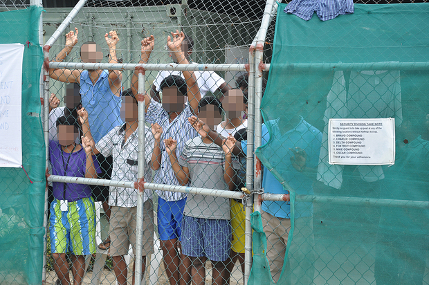 Asylum seekers behind behind a fence on which a sign orders guards to carry the hooked knives used to cut the rope of people who attempt to hang themselves.
