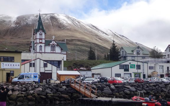 Icelandic town with church and hill dusted with snow.