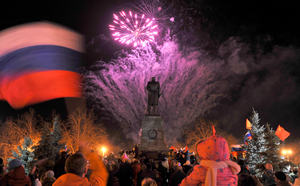 A man waves a Russian flag in Sevastopol as fireworks mark the incorporation of Crimea into the Russian federation.