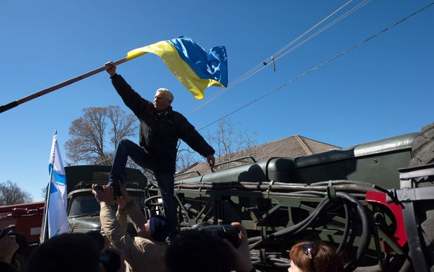 A protester pulls down a Ukrainian flag as pro-Russian forces storm a base in Novofedorivka.