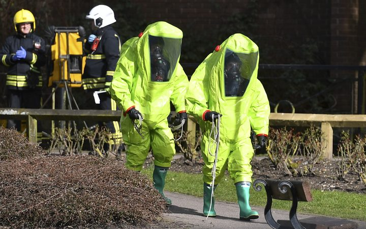 Members of the fire brigade in green biohazard suits work near the bench where a Russian former double-agent and his daughter were found.