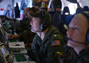 US Navy personnel monitoring search data aboard a P-8A Poseidon over the Indian Ocean.