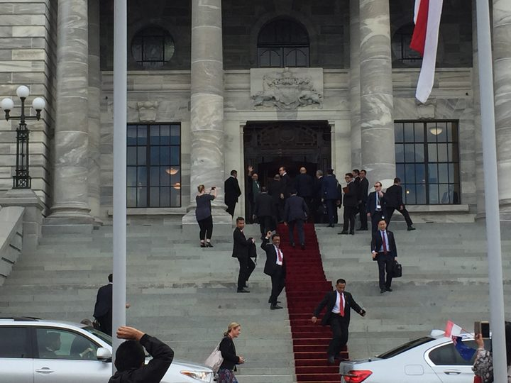 Indonesia's president Joko Widodo disappearing up the steps and into parliament, as his foreign minister Retno Marsudi waves out. 19 March 2018