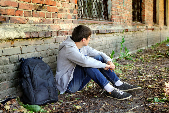 A photo of a sad teenage boy sitting on the grass near an old brick building